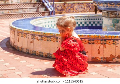 frustrated little girl in a dress of Сarmen near an old fountain