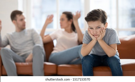 Frustrated little school boy feeling depressed while angry parents fighting at home. Worried upset small son hurt by fathers and mothers break up or divorce, children and family conflict concept.