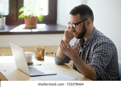 Frustrated male employee discussing contract details over the phone. He is looking at documents in his laptop, holding phone, fling arms in an angry gesture, trying to find solution.