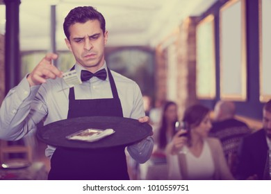 frustrated male waiter looking at a tip on a tray in a cafe
