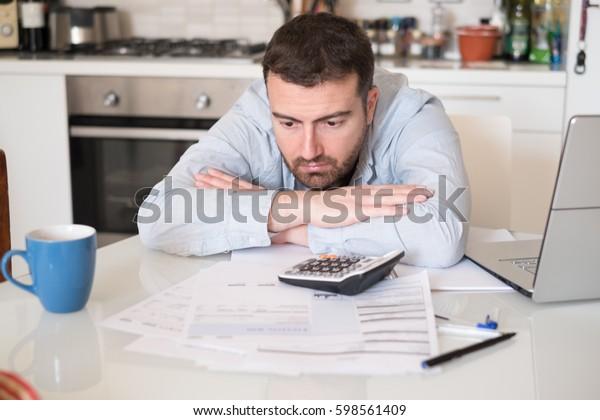 Frustrierter Mann, der Rechnungen und Steueraufwendungen berechnet