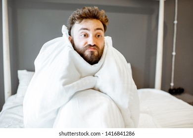 Frustrated man with emotional insanity sitting on the bed covered with white sheets. Concept of insomnia or emotional problems