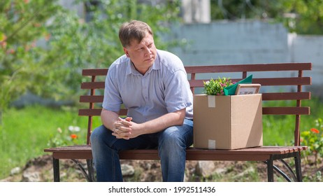 A frustrated man sits on a bench with a box in the park after being fired. - Shutterstock ID 1992511436
