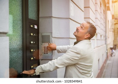 Frustrated man trying to enter a building off the street ringing the bell, pulling the handle and looking up hoping for a response