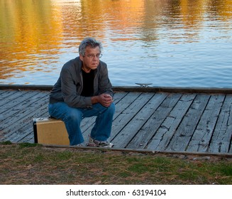 Frustrated man waiting and sitting on a suitacase