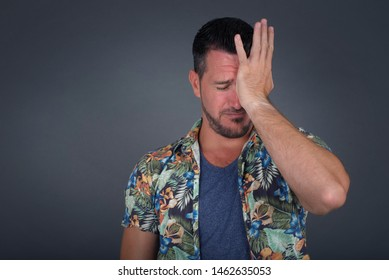 Frustrated man wearing casual clothes holding hand on forehead being depressed regretting what he did, having headache. Confused male with frowned face looking stressful having some pain.