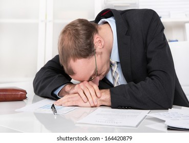Frustrated manager with crisis sleeping at desk.
