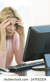 Frustrated mature businesswoman with head in hands looking at computer