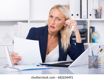 Frustrated mature entrepreneur sitting at office desk with papers and laptop