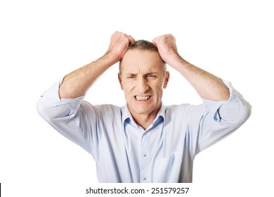 Frustrated mature man pulling his hair.