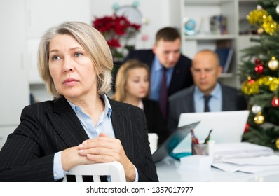 Frustrated mature woman sitting at office on background with working colleagues