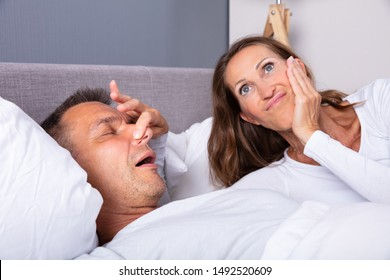 Frustrated Mature Woman Trying To Stop Man's Snoring With Her Finger While Sleeping On Bed