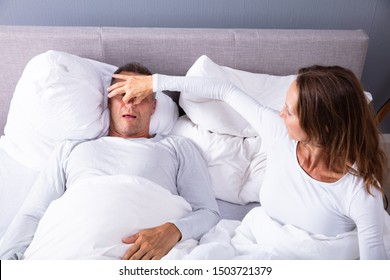 Frustrated Matured Woman Trying To Stop Man's Snoring With Her Finger While Sleeping On Bed