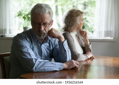 Frustrated middle aged family couple ignoring each other after arguing. Quiet annoyed elder husband and wife sitting separately, going through quarrel, conflict, bad marriage or relationship problem.