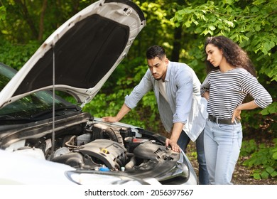 Frustrated middle-eastern couple having broken car while countryside trip, puzzled arab guy and lady checking engine, sad mixed race family stuck in the middle of road, trying to fix auto