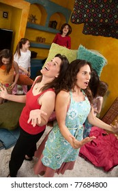 Frustrated mom and babysitter among misbehaving little girls at a sleepover