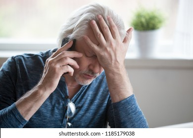 Frustrated older mature retired man feeling upset desperate talking on the phone having problems debt, stressed sad middle aged male depressed by hearing bad news during mobile conversation at home