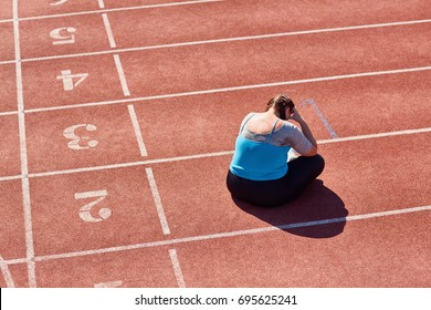 Frustrated over-sized woman sitting on racetrack and crying after training