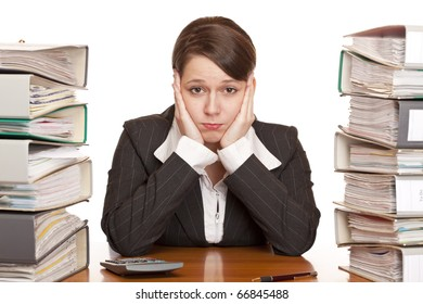 Frustrated overworked business woman in office between folder stack. Isolated on white background.