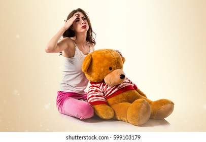 Frustrated pretty brunette girl with pajamas on ocher background