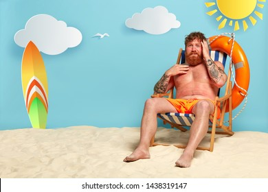 Frustrated red haired man sunbathes at sandy beach, has headache after sunstroke, wears orange shorts, sits at deck chair, has active summer rest, red sunburned skin from sun ultaviolet rays