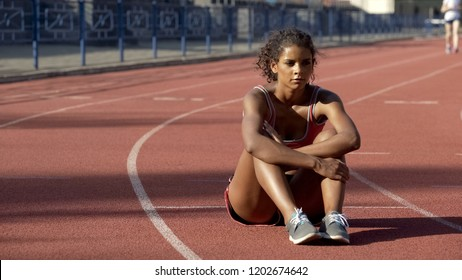 Frustrated with results biracial sportswoman lonely sitting in middle of track