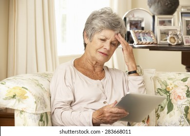 Frustrated Retired Senior Woman Sitting On Sofa At Home Using Digital Tablet
