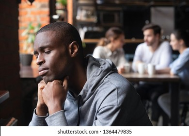 Frustrated sad african american guy sitting alone in cafeteria feels lonely people avoid communication with him because of his skin color, unhappy man outcast suffer from racial discrimination concept
