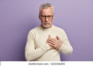 Frustrated senior bearded male pensioner holds hands on chest, has heart attack, sudden stroke, cardio problems, needs medicine, wears spectacles and white sweater. Old people and health concept