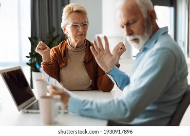 Frustrated senior couple arguing about their home finances at home.