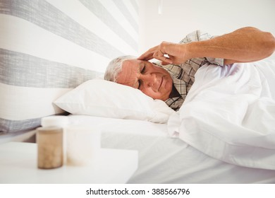 Frustrated senior man lying on bed in bedroom