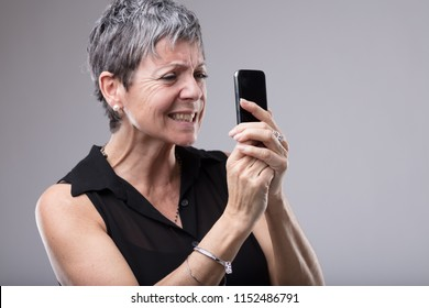 Frustrated senior woman gnashing her teeth as she grips her mobile phone tightly in her hands while reading text message