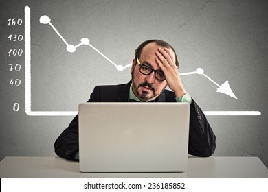 Frustrated stressed business man sitting at table in front of computer with financial market chart graphic going down on grey office wall background. Poor economy concept. Face expression, emotion