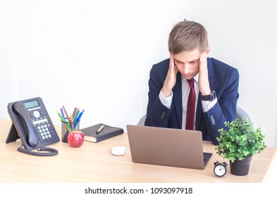Frustrated stressed business man working on laptop computer at the office.