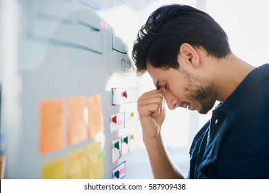 Frustrated, stressed designer struggle for new project ideas banging his head against whiteboard at office