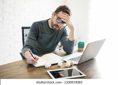 Frustrated and stressed male writer sitting with laptop and writing in a book