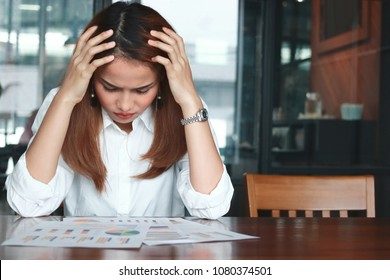 Frustrated stressed young Asian business woman analyzing paper work or charts in workplace. Thinking and thoughtful concept.