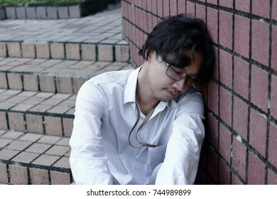 Frustrated stressed young Asian business man feeling tried or disappionted.
