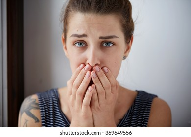 Frustrated stressed young woman. Headshot unhappy overwhelmed girl having headache bad day keeps hands on face out isolated on wall background. Negative emotion face expression feelings perception