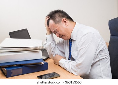 Frustrated, stressful and tired Asian business manager seated behind desk in office