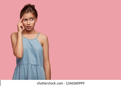 Frustrated student keeps finger on temple, frowns face in displeasure, tries to find solution in mind, ponders how solve problem, wears denim dress, models over pink wall with copy space aside