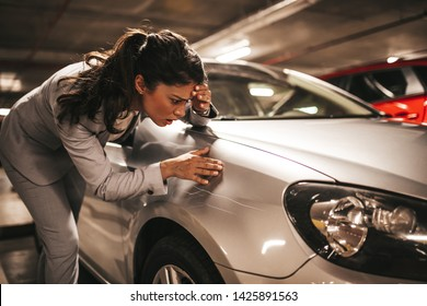 Frustrated and terrified young businesswoman looking at her scratched car.