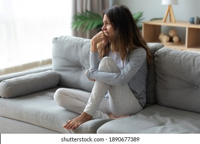 Frustrated unhappy woman crying, sitting on couch at home alone, thinking about personal problem, break up with boyfriend or divorce, need psychological help, feeling lonely and depressed