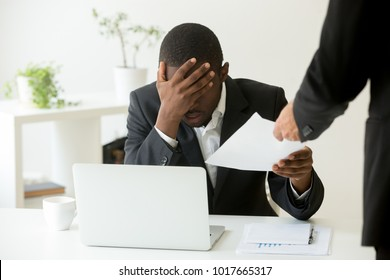 Frustrated upset african american office employee receiving dismissal notice at workplace, depressed bankrupt black entrepreneur getting fired from work, distraught by notification warning about debt