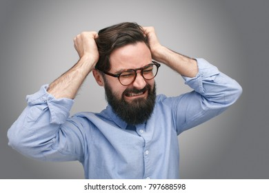 Frustrated and upset bearded man in glasses holding head on gray background.
