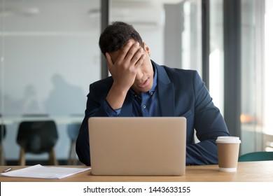 Frustrated upset black business man stressed about computer problem, bad online news financial market crisis, sad desperate african ceo feel loser sit at desk with laptop shocked by bankruptcy debt
