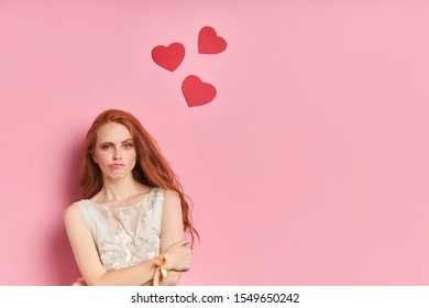 Frustrated woman with auburn hair stand stand looking at camera isolated over pink background. Peple concept