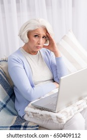 Frustrated woman looking at camera while sitting on sofa or couch. Elderly woman cannot deal with new technologies.
