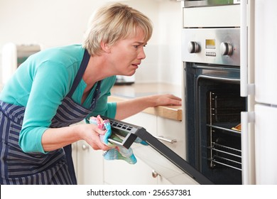 Frustrated Woman Looking In Oven With Disappointed Expression