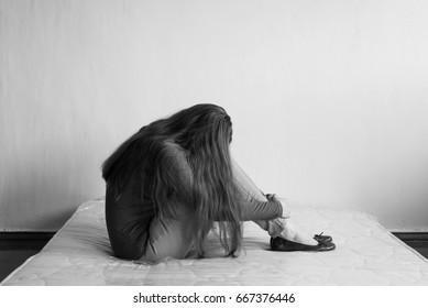 Frustrated woman sitting on a mattress